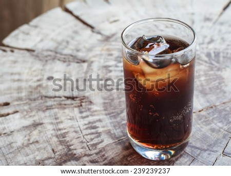 glass of cola with ice cubes on old wood - stock photo