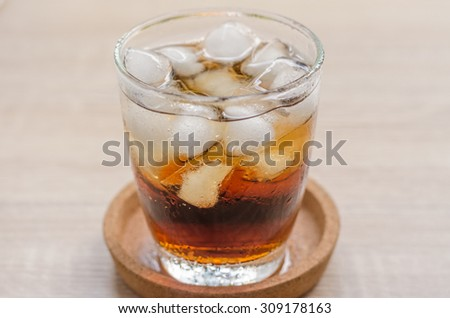 Glass of cola with ice on wooden background - stock photo