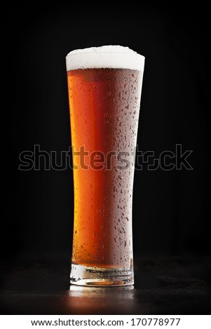 Glass of cold amber beer on a dark background - stock photo