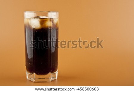 glass of cold drink with ice on brown background closeup - stock photo
