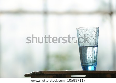 Glass of cold mineral water on the table in front of window - stock photo