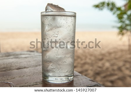Glass of cold mineral water on the table of the beach background - stock photo