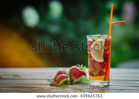 Glass of cold tea with mint,strawberry,lemon, on table, on green background - stock photo