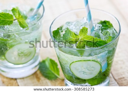 glass of cold water with fresh mint leaves and cucumber with ice cubes on wooden background - stock photo