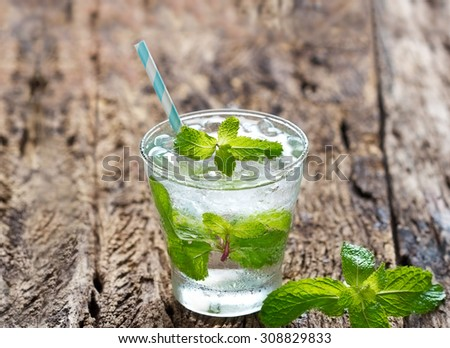 glass of cold water with fresh mint leaves and ice cubes on wooden background - stock photo