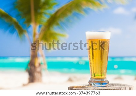 glass of cool beer on table near beach - stock photo