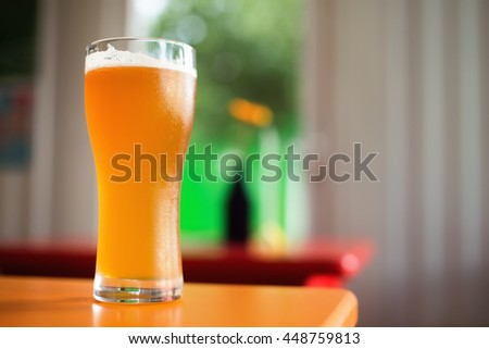 Glass of craft beer on table in bar. Colorful background. Shallow depth of field - stock photo
