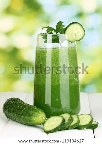 Glass of cucumber juice on wooden table, on green background - stock photo