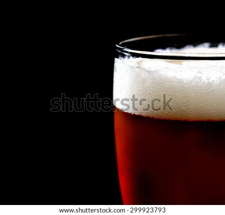 glass of dark beer on a black background - stock photo