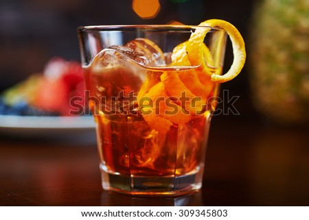 glass of delicious alcoholic cocktails or lemonade with ice, decoration of fresh berries on a wooden table in a bar or restaurant with a beautiful bokeh in the background. soft focus. - stock photo
