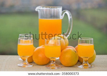 glass of delicious orange juice and oranges on table in garden - stock photo
