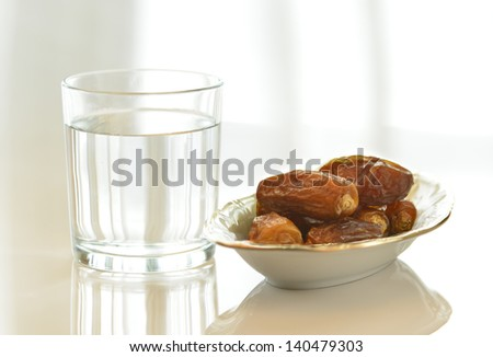 Glass of drinking water and dates - stock photo
