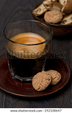 glass of espresso and almond cookies on dark background, close-up, vertical - stock photo