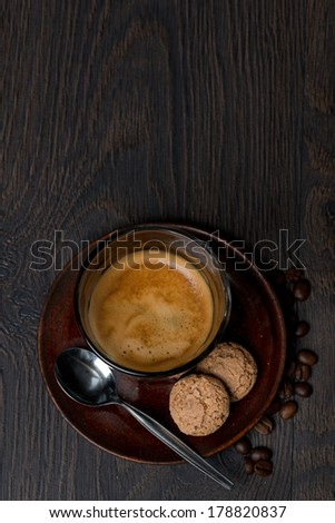 glass of espresso and almond cookies on dark background, top view, vertical - stock photo