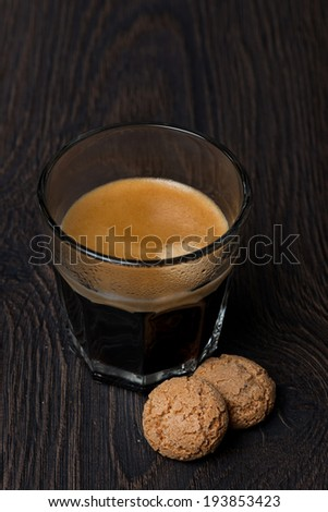 glass of espresso and almond cookies, selective focus, vertical - stock photo