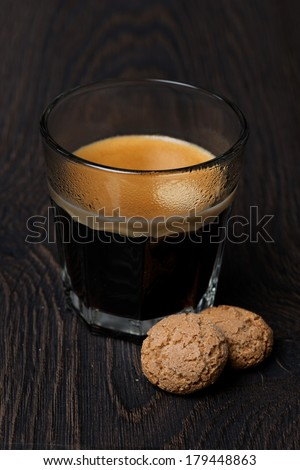 glass of espresso and almond cookies, vertical - stock photo