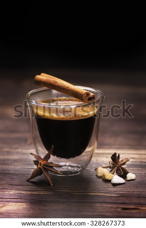 Glass of espresso coffee with spices on wooden background. Selective focus. Toned image - stock photo