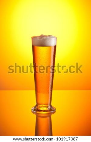 glass of foamy beer over golden background - stock photo