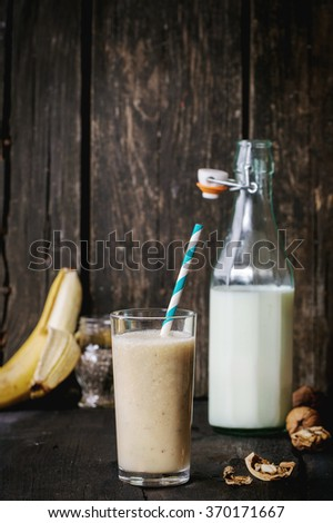 Glass of fresh Banana smoothie with retro cocktail tube, served with bottle of milk, open banana, chia seeds and walnuts over dark wooden table. Rustic style with retro filter effect - stock photo