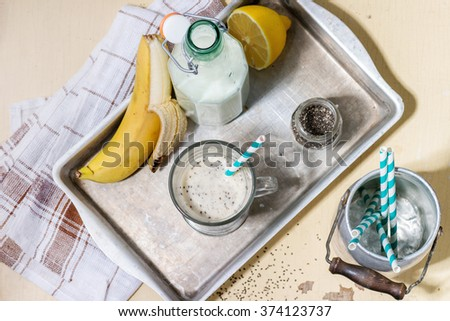 Glass of fresh Banana smoothie with retro cocktail tube, served with bottle of milk, open banana, jar of chia seeds and half of lemon on aluminum tray over white wooden table. Rustic style. Flat lay - stock photo