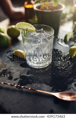 Glass of fresh cocktail drink with lemon slice and ice cubes on a black board. - stock photo