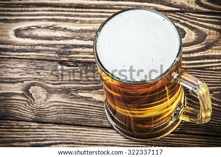 glass of fresh lager beer on a wooden table - stock photo