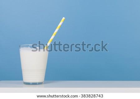 Glass of fresh milk with drinking straw - stock photo