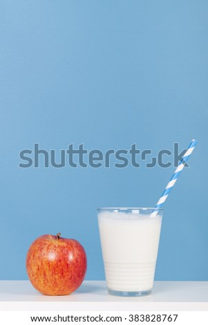 Glass of fresh milk with drinking straw and apple - stock photo