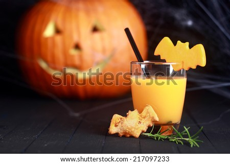 Glass of fresh orange juice decorated for Halloween with a flying bat served with a bat cookie and straw with a pumpkin jack-o-lantern in the background - stock photo