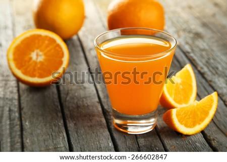 Glass of fresh orange juice on wooden background - stock photo