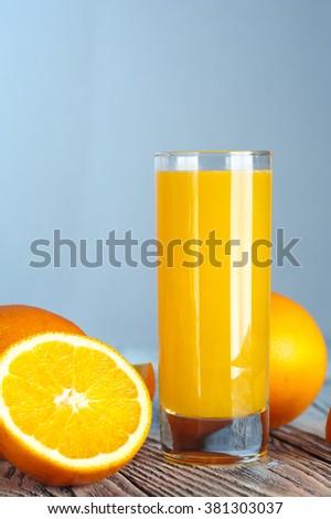 Glass of fresh orange juice with ripe oranges on wooden table - stock photo