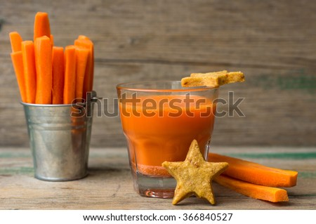 Glass of fresh organic carrot juice, carrot sticks and star shaped carrot cookies  on the wooden background - stock photo