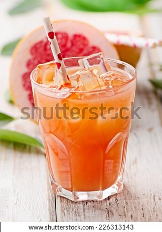 Glass of fresh pink grapefruit juice. Selective focus - stock photo