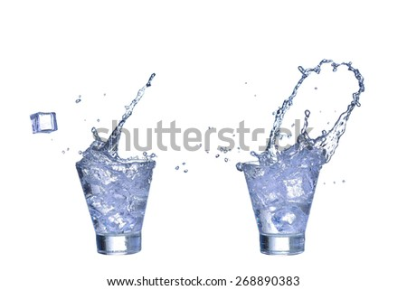 Glass of fresh water, ice cubes make splash isolated on a white background - stock photo