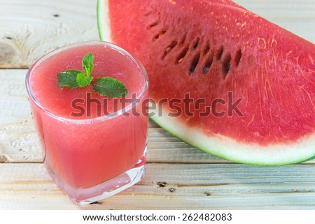 Glass of fresh watermelon juice with mint leaves on wooden table - stock photo