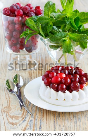 Glass of frozen cranberries. Portion of meringue cake with cream and cranberries - stock photo