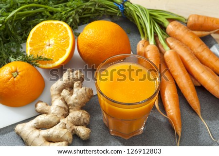 Glass of fruit juice with orange, carrots and ginger on a cutting board - stock photo