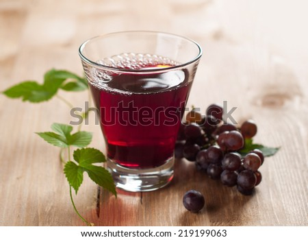 Glass of grape juice with grapes on the background, selective focus - stock photo