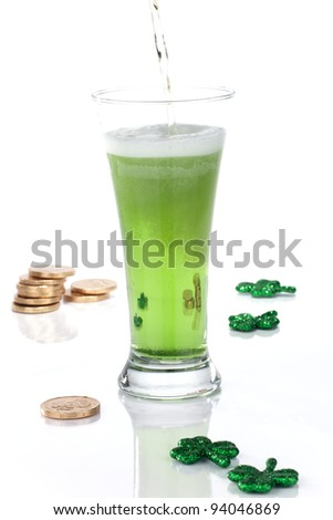 Glass of green beer for St Patrick's Day surrounded with gold coins and shamrock ornament - stock photo