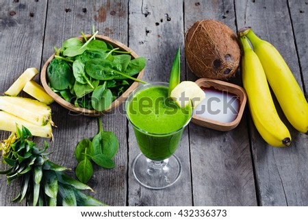 Glass of green fresh juice, and the ingredients from it was made. Smoothies with spinach, banana, coconut water, pineapple on gray wooden table. - stock photo