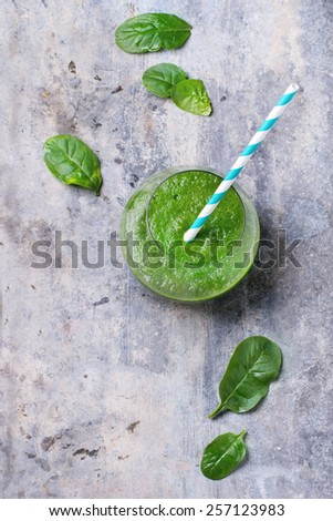 Glass of green smoothie, served with cocktail tube and baby spinach leaves over tin surface. Top view. - stock photo