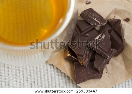 Glass of green tea and a slice of chocolate - stock photo