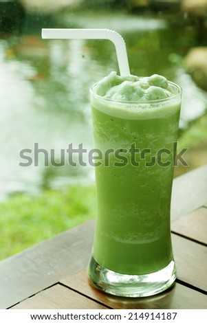 glass of green tea frappe on wooden table in garden. - stock photo
