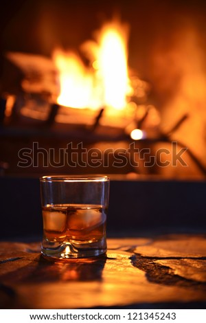 glass of hard liquor with ice cubes in front of the fireplace at night - stock photo