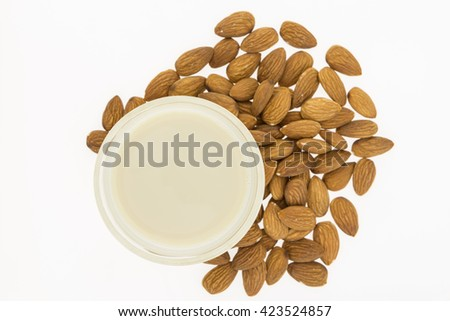 Glass of homemade almond milk and almonds, on white background - stock photo