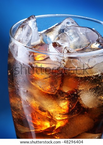 Glass of ice cola on a blue background - stock photo