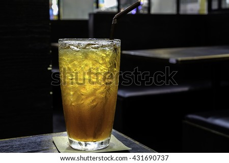 Glass of ice tea with ice on table in restaurant. - stock photo