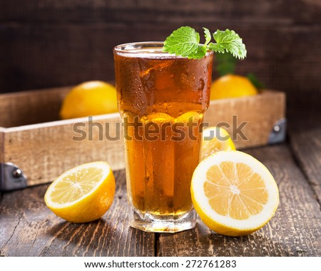 glass of ice tea with mint and lemon on wooden table - stock photo