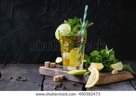 Glass of Iced green tea with lime, lemon, mint and sugar cubes on wooden chopping board over old wooden table. Dark rustic style. - stock photo