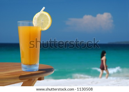 Glass of Juice and Walking Woman Against Tropical Sea - stock photo